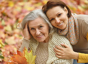 Older woman being hugged by daughter amongst autumn leaves, estate law