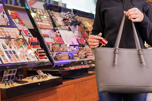 woman shoplifting nail polish into purse